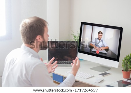 Man in front of computer making video call with doctor at home. Telematic medical appointment concept. Man talking to doctor through webcam #1719264559