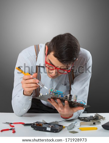 Man in red-framed glasses fixing a computer mother board, gray background #171928973