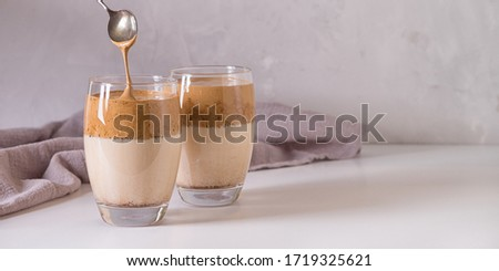 Iced frothy drink Dalgona Coffee, trend korean drink latte espresso with coffee. Gray concrete background. #1719325621