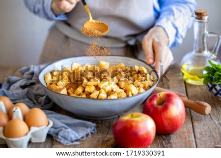 Add a spoonful of cinnamon to the filling of the cake. Cinnamon for apple strudel. Sliced ​​apples with raisins and cinnamon. Cooking a pie. Apple pie. Cinnamon flies in a bowl with apples #1719330391