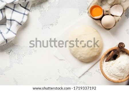 Dough and ingredients for the preparation of pasta, dough, eggs, flour, water and salt on a light rustic old table. Top view. #1719337192