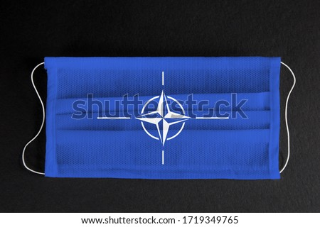 Coronavirus covid pandemic in NATO countries. Flag of NATO printed on medical mask on black background.  Covid-19 outbreak, spread of corona virus in countries of NATO.