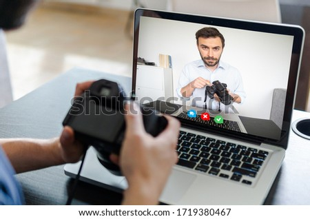 Back view of caucasian man follow a online photography course. Man using laptop for a online lesson in video call.