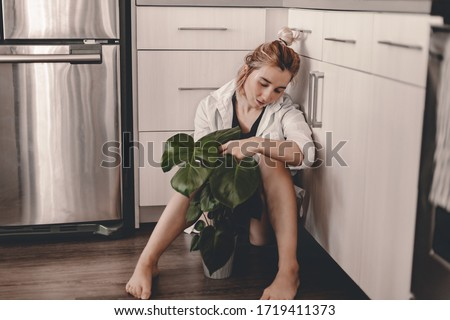 Plant lady sits on the floor in the kitchen and watering home plant. Large green monstera plant, white kitchen. Water pouring, water drops. Lifestyle kitchen. Barefoot girl in white shirt. Plant mom #1719411373