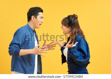 Profile side view portrait of two attractive angry aggressive nervous people having fight anger blame isolated over vivid shine bright orange background. Negative emotions concept. Royalty-Free Stock Photo #1719411484