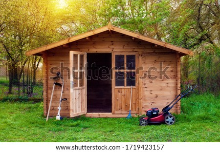 Hovel after work in evening, golden hour. Garden shed (front view) with hoe, string trimmer,  rake and grass-cutter. Gardening tools shed. Garden house on lawn in the sunset. Wooden tool-shed.  #1719423157