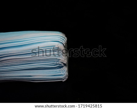 Layers of blue medical face mask and black background.Prevention for flu and coronavirus. Face mask in the pile.