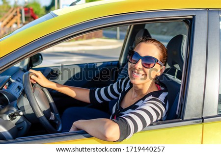 Girl drives a yellow car on a sunny day. #1719440257