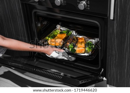 woman opens the oven. hand on the oven door. baked trout in the oven. woman is cooking dinner in the oven with baked salmon. #1719446620