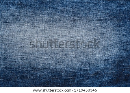 Jeans backdrop pattern with vignetting. Classic blue texture. Background of denim canvas. Design element. Copy space.