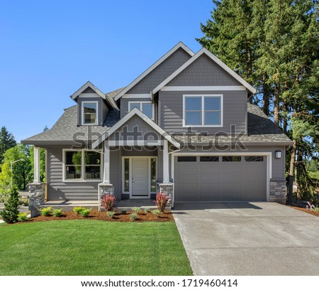 Beautiful new home exterior with two car garage and covered porch on sunny day Royalty-Free Stock Photo #1719460414