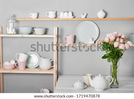 Utensils, bouquet of roses and mugs on shelf. Dishes in cupboard in kitchen.Kitchenware on wooden shelves.Kitchen interior background.Opened cupboard with kitchenware inside.Mother's Day greeting card #1719470878