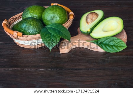 ripe avocados in a basket and avocado halves on a chopping board close-up. background with whole avocados, avocado halves and avocado leaves. #1719491524