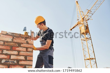 Installing brick wall. Construction worker in uniform and safety equipment have job on building. #1719495862