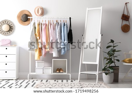 Rack with stylish women's clothes and mirror indoors. Interior design Royalty-Free Stock Photo #1719498256