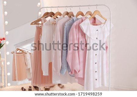 Rack with stylish women's clothes and mirror indoors. Interior design Royalty-Free Stock Photo #1719498259