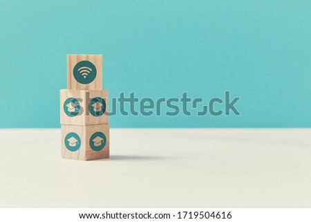 E-learning. Virtual education. Distance learning. Online seminar, webinar. Stack of wooden cubes with cap, wifi signs #1719504616
