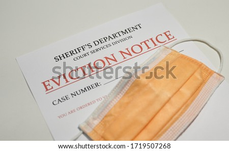 Yellow facial mask laying on top of the eviction note Royalty-Free Stock Photo #1719507268