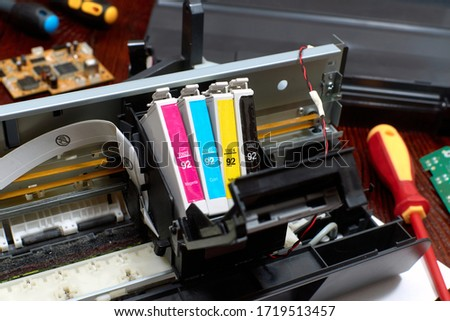 The printer is disassembled. Repair of the printer. Color ink cartridges for an inkjet printer. An inkjet printer motherboard. Maintenance of inkjet printers #1719513457