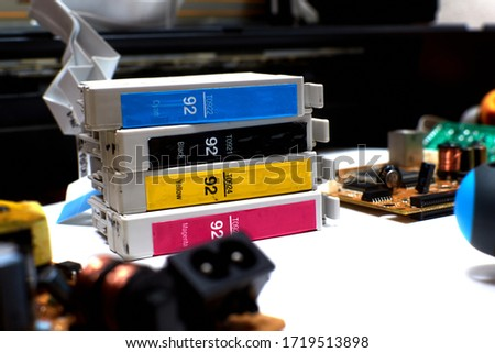 The printer is disassembled. Repair of the printer. Color ink cartridges for an inkjet printer. An inkjet printer motherboard. Maintenance of inkjet printers #1719513898