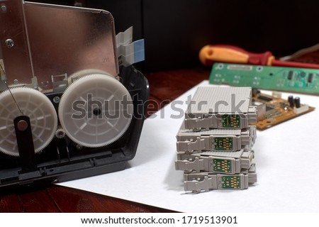 The printer is disassembled. Repair of the printer. Color ink cartridges for an inkjet printer. An inkjet printer motherboard. Maintenance of inkjet printers #1719513901