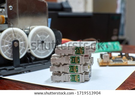 The printer is disassembled. Repair of the printer. Color ink cartridges for an inkjet printer. An inkjet printer motherboard. Maintenance of inkjet printers #1719513904