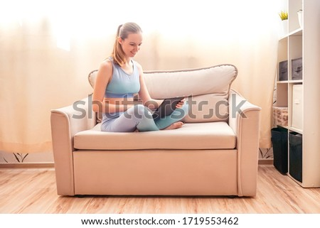 Fitness woman use laptop in sofa after training. #1719553462
