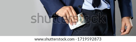 Man putting bribe into pocket on grey background, closeup. Banner design #1719592873