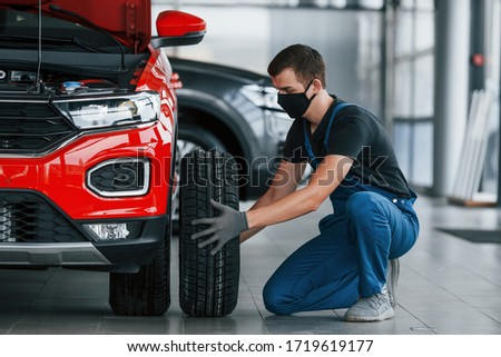 Man in uniform changing tire of automobile. Conception of car service. Royalty-Free Stock Photo #1719619177