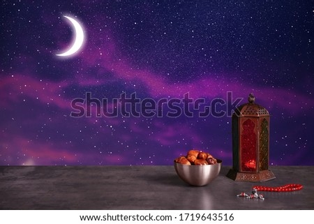 Traditional Ramadan lantern, dates and prayer beads on table. Muslim holiday #1719643516
