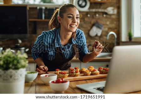 Young smiling woman preparing food in the kitchen while live streaming over laptop in the kitchen.  #1719651991