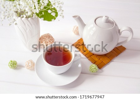 White ceramic cup and tea pot, vase with flowers on white wooden table background. Beautiful setting the table for Breakfast and tea time. The concept of Beginning of the day good morning.