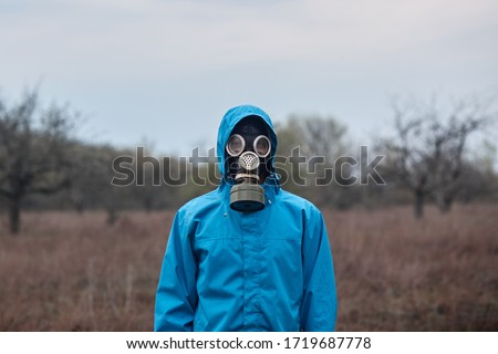 Outside picture of stalker wearing blue jacket and gas mask, spending time alone, being at 30 km exclusion zone, doing illegal things, looking directly at camera. People and adrenaline concept.