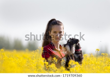 Pretty teenage girl holding cute dog miniature schnauzer in rapeseed with yellow blooming flowers in springtime #1719709360