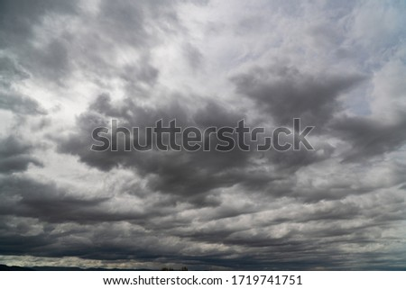 The dark clouds is look like a big black smoke from erupting volcano. Storm is coming before heavy rain storm. On the sky is covered all over by the clouds. #1719741751