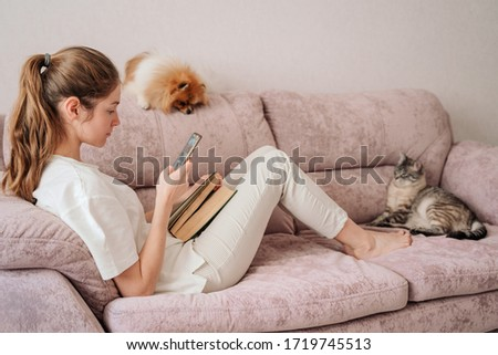attractive young woman sitting on the sofa reading a book and was distracted by the phone. the cat and dog are resting next to the owner. beautiful living room