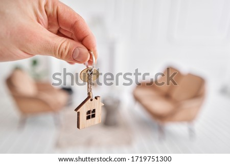 Men hand holding key with house shaped keychain. Modern light lobby interior. Mortgage concept. Real estate, moving home or renting property. Royalty-Free Stock Photo #1719751300