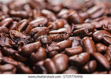Close up to a heap of coffee beans. Macro photography of fresh roasted coffee beans high resolution. Detailed macro picture on roasted coffee beans.  Close-up of brown coffee beans background  image