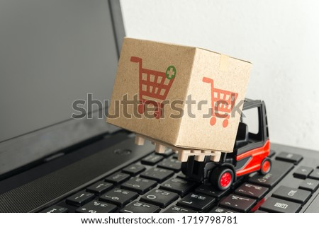 Forklift lift parcel carton box with shopping trolley cart printing on laptop computer white wall background. E-commerce or online shopping, logistic inventory control, cash on delivery (COD) concept. #1719798781