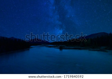 Starry Sky Reflected in River Over Mountain Wilderness Landscape #1719840592