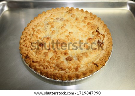 A freshly baked dutch apple pie on a cookie sheet.