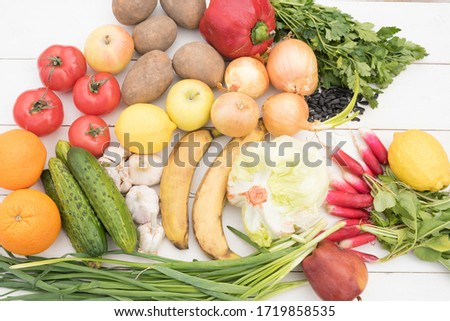 vegetables and fruits lie on a white wooden table. Flat Lay, Copy Space. potatoes, onions, radishes, tomatoes, parsley, cucumber, pepper, apples, iceberg salad, lemon, garlic, banana, orange #1719858535