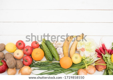 vegetables and fruits lie on a white wooden table. Flat Lay, Copy Space. potatoes, onions, radishes, tomatoes, parsley, cucumber, pepper, apples, iceberg salad, lemon, garlic, banana, orange #1719858550
