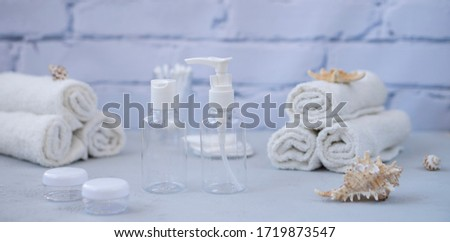Plastic containers. Spa composition, recreation and hospitality. Beauty and skin care concept.  Plastic bottles, lens containers and white towels on a light background #1719873547
