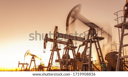 Oil pump rig. Oil and gas production. Oilfield site. Pump Jack are running. Drilling derricks for fossil fuels output and crude oil production. War on oil prices. Global coronavirus COVID 19 crisis. #1719908836