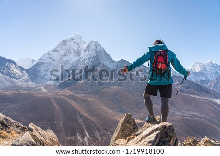 Trail runner standing on top of mountain and looking to Ama Dablam mountain peak in Dingboche village, Everest base camp trekking route, Nepal, Asia #1719918100