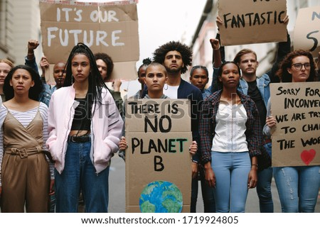 Group of activists with banners protesting to save earth. Men and women rebellions doing a silent protest over global warming and pollution. #1719924805