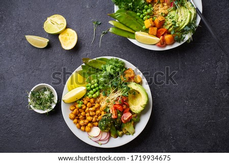 Healthy vegetarian lunch bowl with avocado, chickpeas, quinoa and vegetables, garnished with microgreens and nut dressing. Flat lay on dark concrete background. #1719934675
