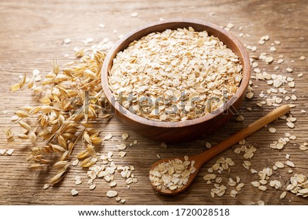 oatmeal flakes and ears of oat on wooden table #1720028518