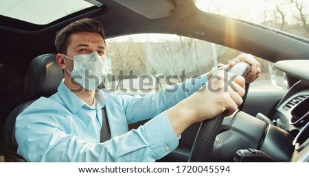 Man driving a car wearing on a medical mask during an epidemic, a driver in a mask, protection from the virus. Coronavirus, disease, infection, quarantine, covid-19, pandemic, epidemic concept #1720045594